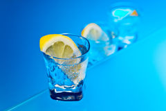Gin with lemon on a glass table Stock Images