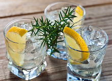 Gin with lemon and ice. On a old wooden table Royalty Free Stock Photos