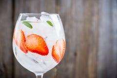 Gin mit Erdbeere und Eis im Weinglas stockfoto
