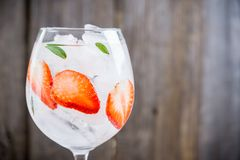Gin with strawberry and ice in wine glass stock photo