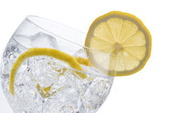 Gin and tonic. In a balloon glass garnished with lemon and isolated over awhite background royalty free stock photo