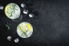 Gin and tonic cocktail. Alcohol drink gin tonic cocktail with lemon, rosemary and ice on rustic black stone table, copy space, top view. Iced drink with lemon stock photography