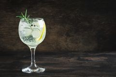 Gin and tonic cocktail. Alcohol drink gin tonic cocktail with lemon, rosemary and ice on rustic black wooden table, copy space. Iced cocktail drink with lemon stock image