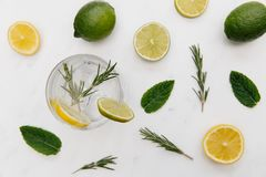 Gin tonic cocktail drink with green lime white background. Gin tonic cocktail drink with green lime on white background stock photo