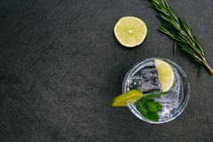 Gin tonic cocktail drink with ice glass green lime dark background. Gin tonic cocktail drink with ice glass green lime on dark background royalty free stock image