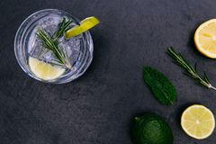 Gin tonic cocktail drink with ice glass green lime dark background. Gin tonic cocktail drink with ice glass green lime on dark background stock photo