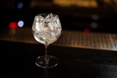 Gin Tonic coctailexponeringsglas som är fullt av iskuber som står på stången c royaltyfria foton