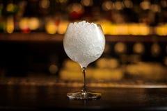 Gin Tonic coctailexponeringsglas som är fullt av krossad is som står på stången arkivbild