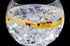 Gin tonic. Glass of gin and tonic on slate plate with black background royalty free stock images