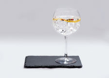 Gin tonic. Glass of gin and tonic on slate plate with white background stock photo