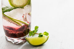 Gin tonic with lime, ice and red fruit Royalty Free Stock Photography
