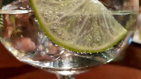 Gin and tonic in macro view. Gin and tonic with slice of lime in macro view royalty free stock images