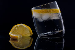 Gin and tonic with a slice of lemon. Gin and tonic or vodka and tonic with a slice of lemon over black Royalty Free Stock Photography