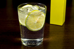 Gin and tonic. Spirit cocktail over dark wood table Royalty Free Stock Images