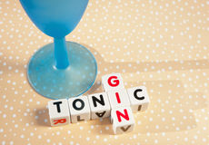 Gin and tonic. Text 'gin and tonic' inscribed on small white cubes and arranged jigsaw style next to a blue glass, bright spotted background Royalty Free Stock Photography