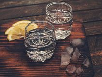 Gin tonic, vodka or rum with ice and lemon on wooden table. Retr Stock Photos