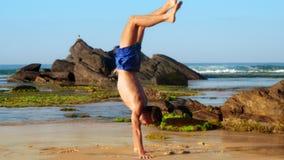 A ginasta considerável anda nas mãos ao longo da areia molhada litoral filme