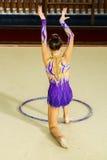 A ginasta da menina executa com uma aro na competição Foto de Stock