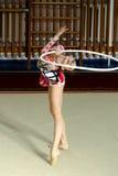A ginasta da menina executa com uma aro na competição Fotos de Stock Royalty Free