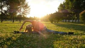 A ginasta da menina senta-se em uma corda na grama em um parque da cidade na natureza e faz-se curvaturas laterais aos pés imagens de stock royalty free