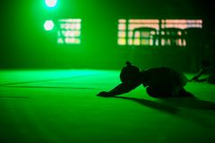 A ginasta do atleta da moça executa elementos acrobáticos em uma luz cênico verde imagens de stock