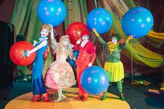 Ginasta do palhaço do close-up, andando em suas mãos Um grupo de palhaços na composição com os balões coloridos enormes fotografia de stock royalty free
