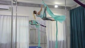 A ginasta executa um exercício na parte traseira que pendura a seda aérea filme