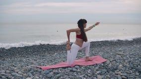 A ginasta fêmea está esticando os músculos e os tendões na costa de mar, praticando a ioga vídeos de arquivo