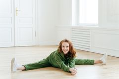 A ginasta fêmea no sportswear, faz a separação do pé, senta-se no assoalho, poses na sala da ioga, tem exercícios do exercício, e imagens de stock royalty free