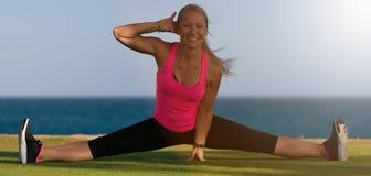 A ginasta fêmea no sportswear, faz a separação do pé, senta-se na grama na costa do oceano, levanta na ioga imagem de stock royalty free