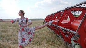 Ginasta flexível da menina no vestido no campo do outono na estação da colheita do pão perto da ceifeira de liga vídeos de arquivo