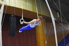Ginasta masculina que executa em anéis ginásticos estacionários Foto de Stock Royalty Free
