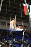 Ginasta masculina que executa em anéis ginásticos estacionários Imagem de Stock