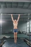 Ginasta masculina que executa o pino em barras paralelas Fotos de Stock Royalty Free