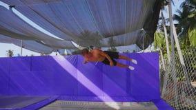 A ginasta muscular do homem no short est? saltando no trampolim que faz para tr?s o salto mortal filme