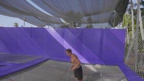 Ginasta profissional que salta no trampolim e que faz truques no movimento lento filme