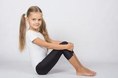 Ginasta seis anos que sentam-se abraçando seus pés dos joelhos Imagem de Stock