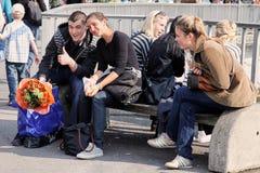 Ginebra, Suiza - mayo de 2012: El grupo de gente joven que se sienta en el banco de la calle delante del río Pares del amigo, mA fotografía de archivo