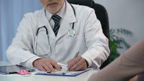 Ginecólogo que consulta al paciente femenino, medicación que prescribe, la salud de las mujeres almacen de metraje de vídeo