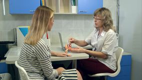 Ginecologo che tiene il modello femminile di anatomia dell'utero e che parla con paziente fotografia stock libera da diritti