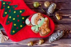 Ginferbread gentil de miel de Noël dans la forme de l'ours dans le chapeau rouge s'étendant sur la chaussette de vacances sur le  Image stock