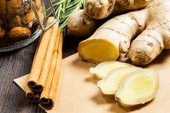 Gingembre, bâtons de cannelle, amandes et romarin - additifs utiles au thé et aux boissons photographie stock libre de droits