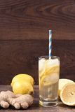 Ginger ale with lemon to accelerate metabolism. Refreshing healthful beverage. Wood background. Stock Photos