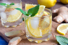Ginger ale soda. With lemon, mint, ginger and ice over rustic wooden background Royalty Free Stock Images