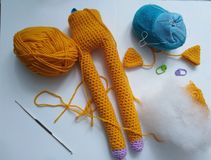 Ginger amigurumi crochet long feet cat in process stock images
