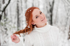 Ginger beautiful girl in white sweater in winter forest. Snow december in park. Portrait. Christmas cute time. Royalty Free Stock Image