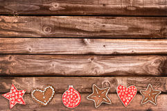 Ginger bread cookies and Christmas ornaments on wooden planks Royalty Free Stock Photo