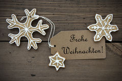 Ginger Bread Stars with Frohe Weihnachten Banner. Ginger Bread Stars with white Decoration and a Label with the German Words Frohe Weihnachten which means Merry royalty free stock image