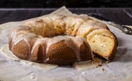 Ginger cake with lemon glaze. Ginger cake drizzled with lemon glaze on a dark wooden background Royalty Free Stock Photo