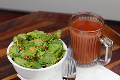 Ginger Carrot Tomato Dressing Watercress Salad. Bowl of ginger carrot tomato watercress salad with a cup of tomato juice. Lunch of watercress salad and a mug of royalty free stock photography